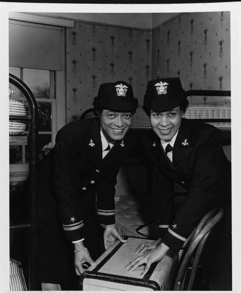 Lt. (j.g.) Harriet Ida Pickens (left) and Ens. Frances Wills close a suitcase after graduating from the Naval Reserve Midshipmen's School (WR) at Northampton, MA, 21 December 1944. They were the Navy's first African-American WAVES officers and graduated with the Northampton school's final class. (U.S. Navy Photograph)