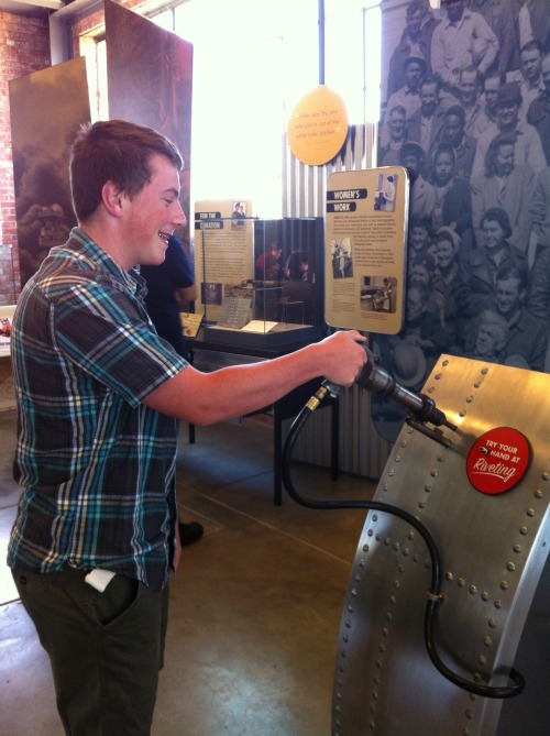 My son humoring his mother and operating the riveting gun exhibit at the Rosie the Riveter WWII Home Front Museum, Richmond, CA (May 2014)