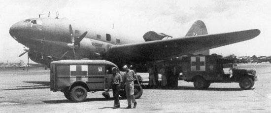 Dodge ambulances standing by C-46 Commando at Clark Field, Manila, Philippine Islands, 29 Sep 1945 (public domain via WW2 Database)