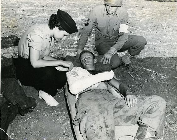 Flight nurse Verona Savinski, 802nd Medical Evacuation Transport Sqd., and Cpl. Claude W. Thomas 3rd Auxiliary Surgical Group, with Pfc. Joe Kirach of Brooklyn N.Y., 504th Parachute Infantry, Italy, 28 October 1943 (US National Archives)