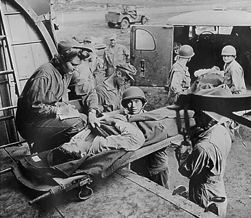 Flight nurse Lt. Mae Olson takes the name of a wounded American soldier being placed aboard a C-47 for air evacuation from Guadalcanal in 1943 (US Air Force photo)