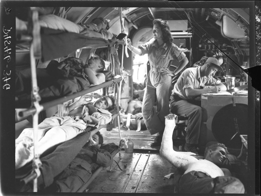 C-46 air evacuation from Manila, Philippine Islands, 1945—flight nurse standing, surgical technician at desk (US Army Air Force photo)