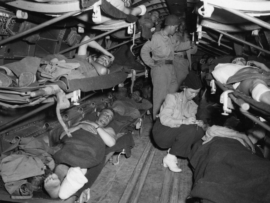Lt. Katye Swope of the 802nd Medical Air Evacuation Transport Squadron checks patients being evacuated from Agrigento, Sicily to North Africa for further medical treatment, 25 July 1943. (US Air Force photo)