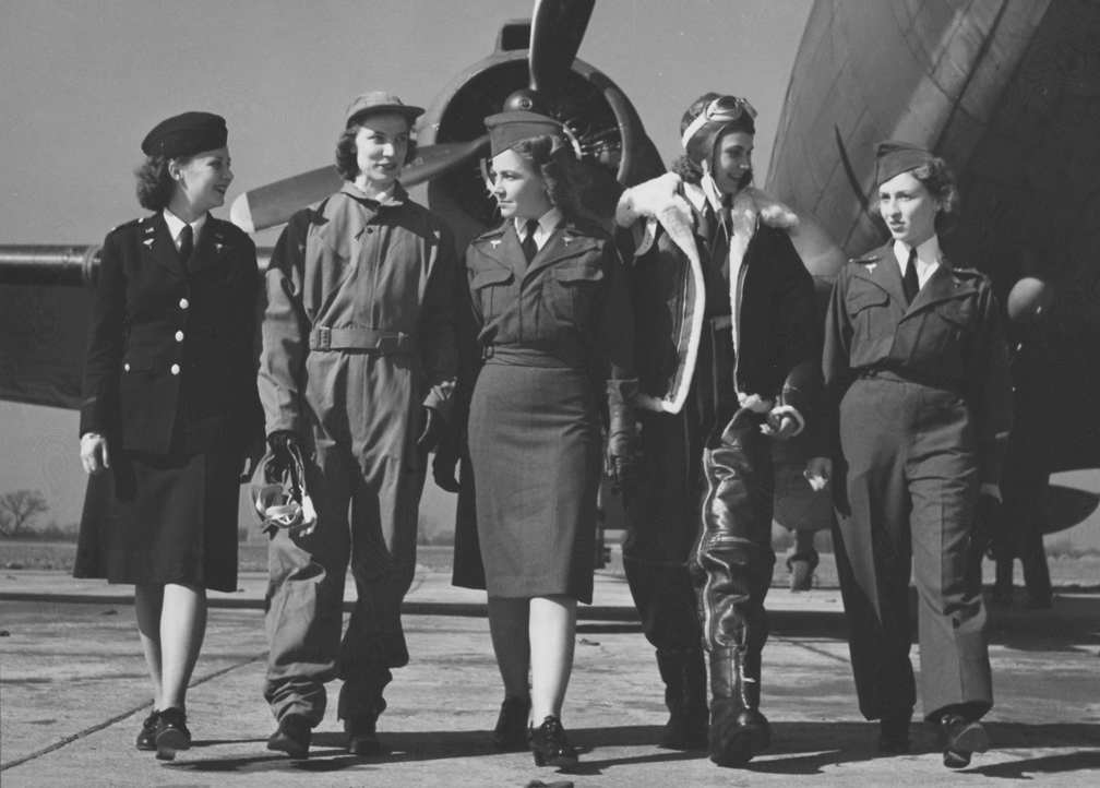 US Army flight nurses in 1943, displaying the various types of Army Nurse Corps uniforms—Lt. Wilma Vinsant, regulation blue winter uniform, Lt. Edith M. Roe; Lt. Ethel Guffey; Lt. Jane Orme in winter flying suit, Lt. Adela Besse in gray flying suit with slacks (US National Archives)