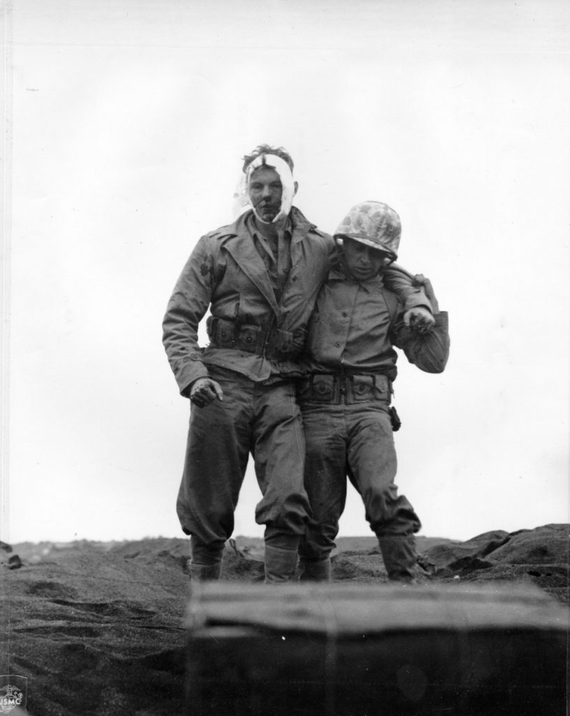 Wounded US Marine being helped by a comrade, Iwo Jima, 20 Feb 1945 (US Marine Corps photo)