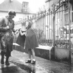 T/Sgt. Joe Trdenic of US 36th Infantry Division receives gift from 11-year-old Therese Grenier in Luxeuil, France, 16 Sept 1944 (US Army Center of Military History)
