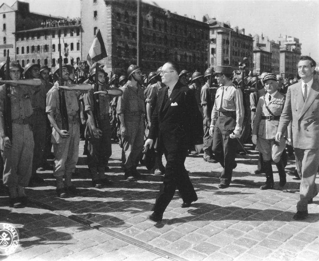 André Diethelm, Jean de Lattre de Tassigny, Emmanuel d'Astier de La Vigerie, and General Monsabert reviewing troops, Marseille, France, 29-31 Aug 1944 (public domain via WW2 Database)