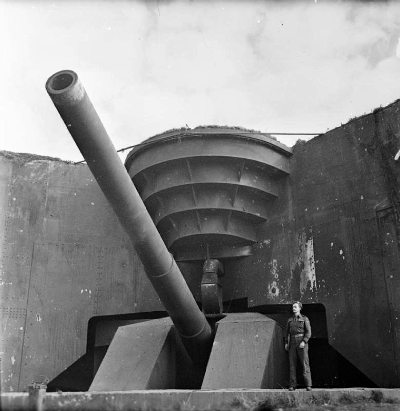Soldier poses next to one of the German coastal guns captured by the Canadians at Cap Gris Nez, France, 1 October 1944 (Imperial War Museum B 10467)