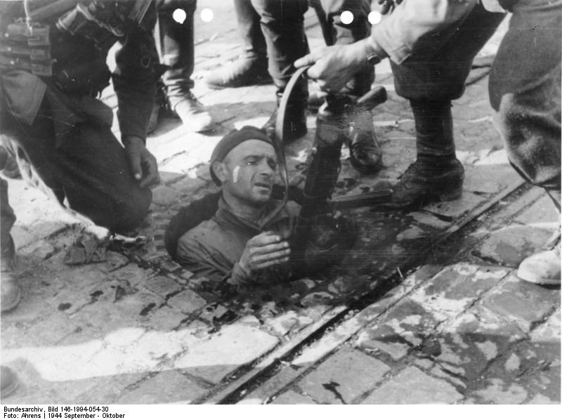 Polish insurgent fighter surrendering from the sewers under Warsaw, 27 September 1944 (German Federal Archive. Photographer: August Ahrens, Bild 146-1994-054-30)
