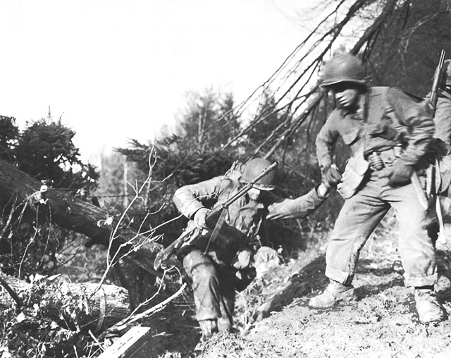 US soldiers struggling up a hill in the Hürtgen Forest, 1944 (US Army Center of Military History)