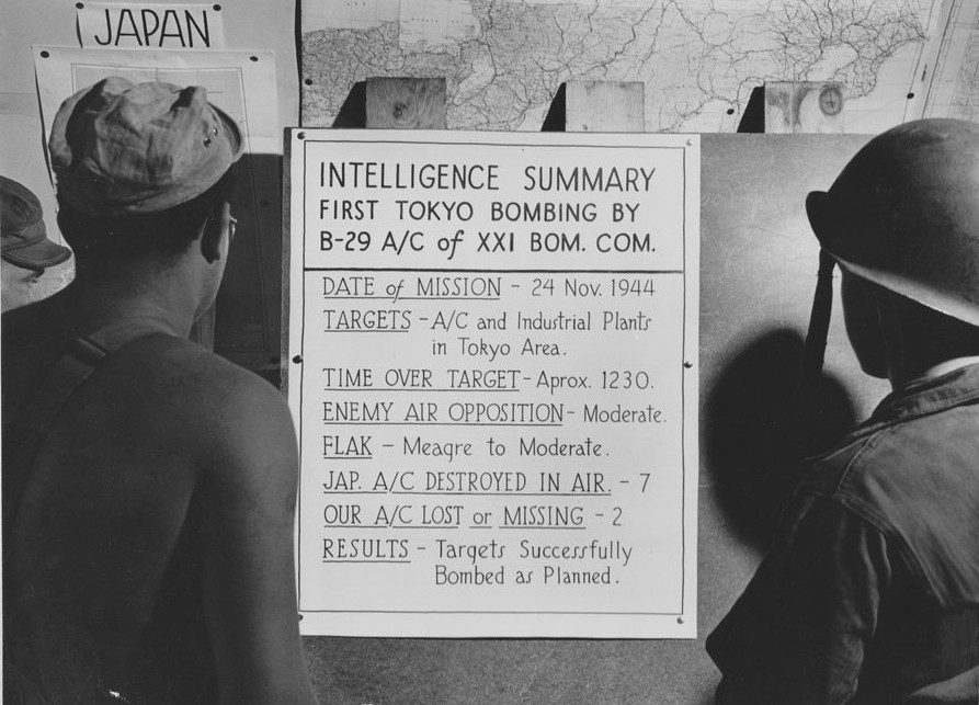 US airmen reading a bulletin announcing their Saipan-based unit's first bombing of Tokyo, Japan on 24 Nov 1944 (US National Archives)