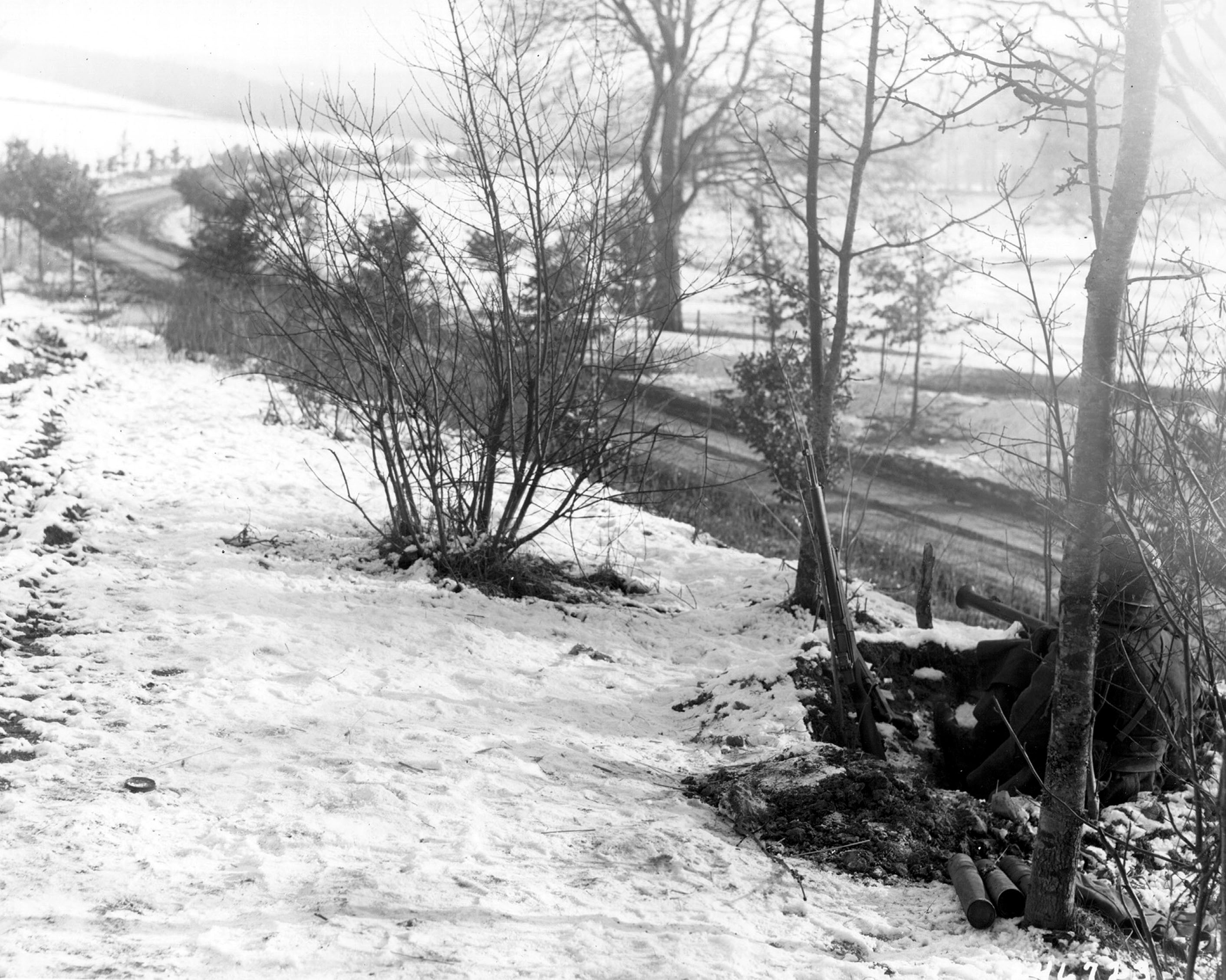 Two soldiers of US 101st Airborne Division with bazookas guard road leading to Bastogne, Belgium, 23 Dec 1944 (US Army Center of Military History)