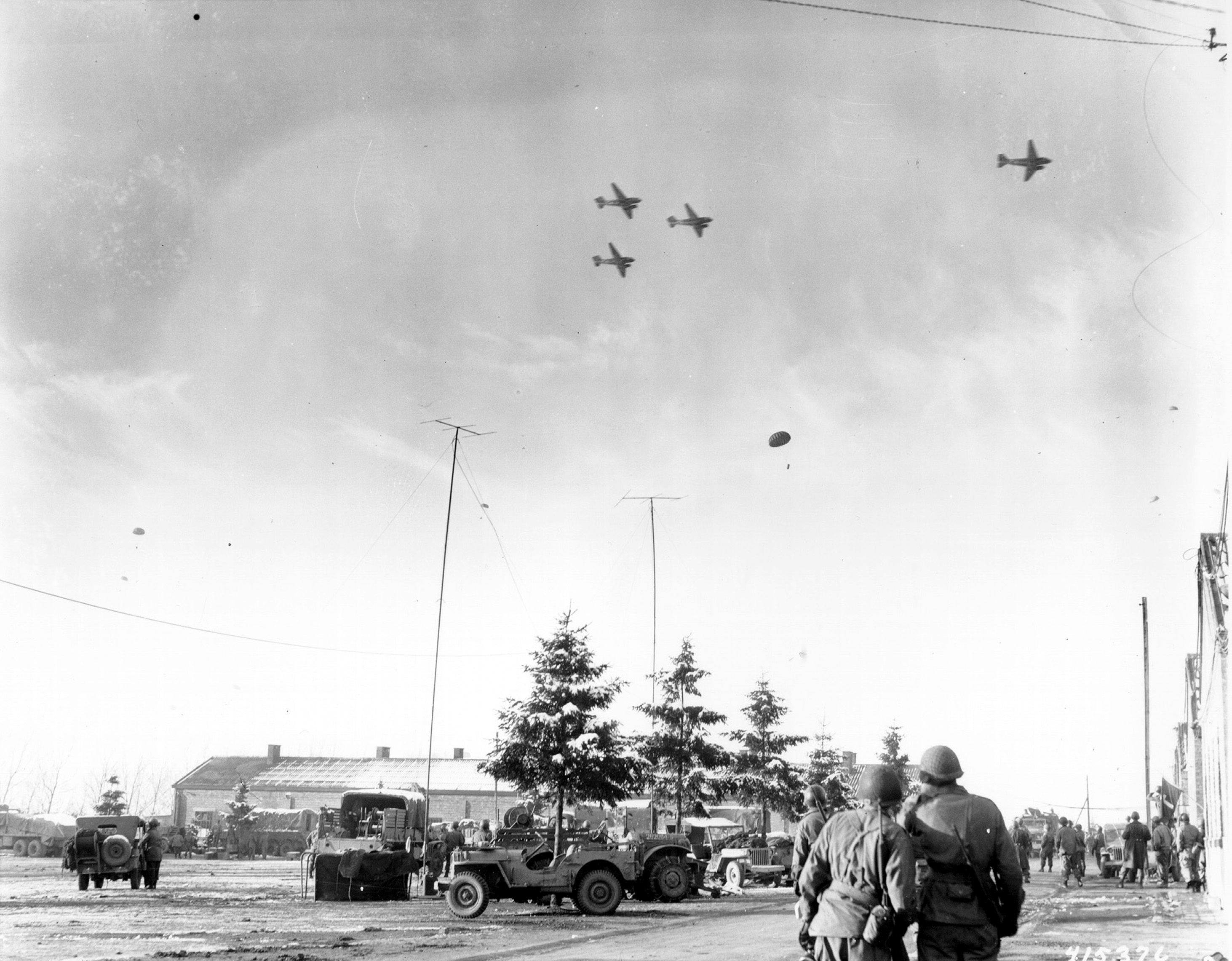 Troops of US 101st Airborne Division watching C-47 Skytrain aircraft delivering supplies to their unit, Bastogne, Belgium, 26 Dec 1944. (US Army Signal Corps)