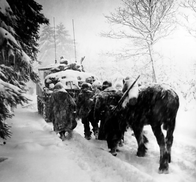 Troops of US 82nd Airborne Division marching behind M4 Sherman tank in a snowstorm toward German occupied town of Herresbach, Belgium, 28 Jan 1945 (US Army photo)