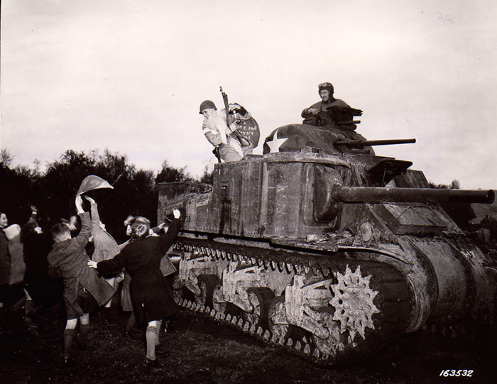 Sgt. Hiram Prouty of US 175th Infantry Regiment dressed as Santa Claus, arriving on a M3 medium tank, Perham Down, England, 5 December 1942 (US Army Signal Corps)