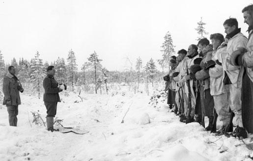 Finnish Army Lieutenant Aarne Juutilainen and his company holding a Christmas service near the Kollaa River, Finland, 24 Dec 1939 (public domain via WW2 Database)