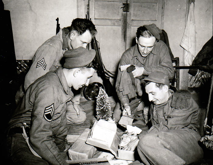 Troops of US 3rd Infantry Division (S/Sgt. John Suchanek, Pfc. Joseph Pierro, Sgt. Charles Myrich, Sgt. Leon Oben) open Christmas gifts from home, Pietramelara, Italy, 16 December 1943 (US Army Center of Military History)