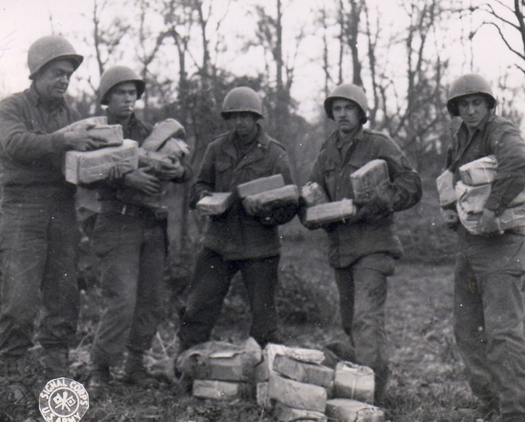 US Army Pfc. W.J. Kessler, Pfc. J.L. Proffitt, Pvt. B. Narter, Cpl. T.J. Barnewski, and Pfc. J. Stoll with Christmas packages from home for their artillery unit, Germany, 26 Nov 1944 (US Army Signal Corps)