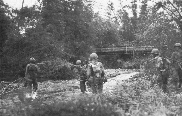 Patrol of the 307th Infantry at a river crossing near Camp Downes in the approach to Ormoc, Leyte (US Army Center of Military History)