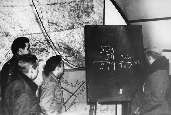 Colonel Dregne of the US 357th Fighter Group gives a briefing to pilots Foy, Storch and Evans at Leiston Army Air Field in England, 14 Jan 1945, showing the 54 victories earned by the group that day (later revised to 56.5 victories), and the group's 549 total victories (Imperial War Museum, Roger Freeman Collection)