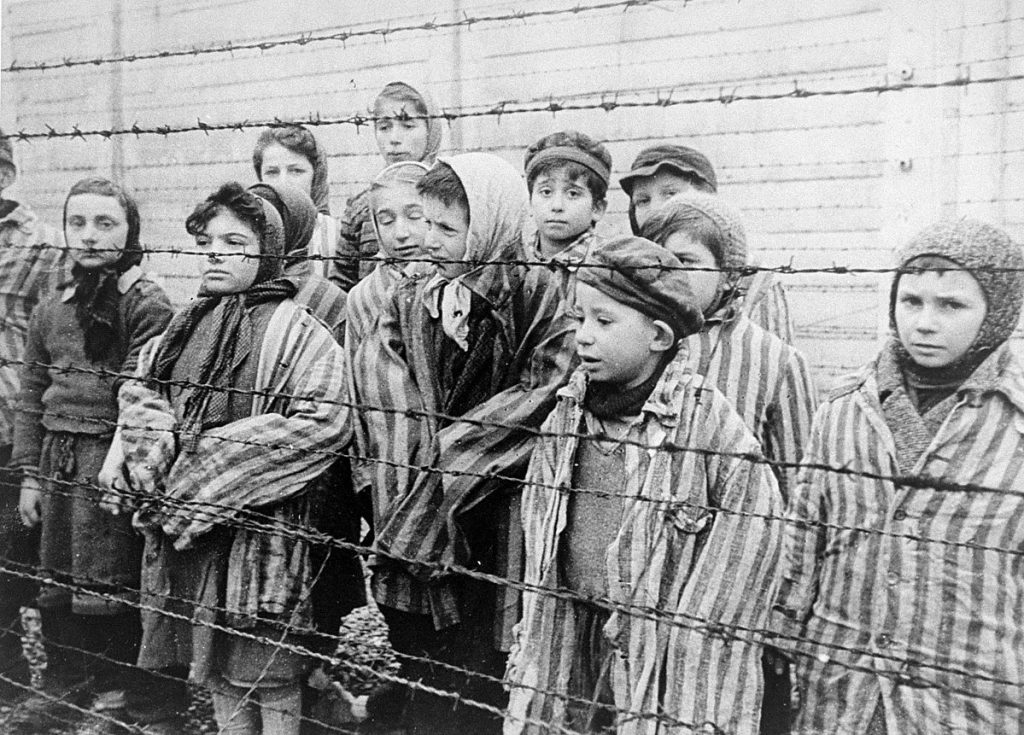 Child survivors of Auschwitz, 27 Jan 1945; Still photograph from Soviet film of the liberation of Auschwitz, taken by the film unit of the First Ukrainian Front (public domain via United States Holocaust Memorial Museum, courtesy of Belarussian State Archive of Documentary Film and Photography)