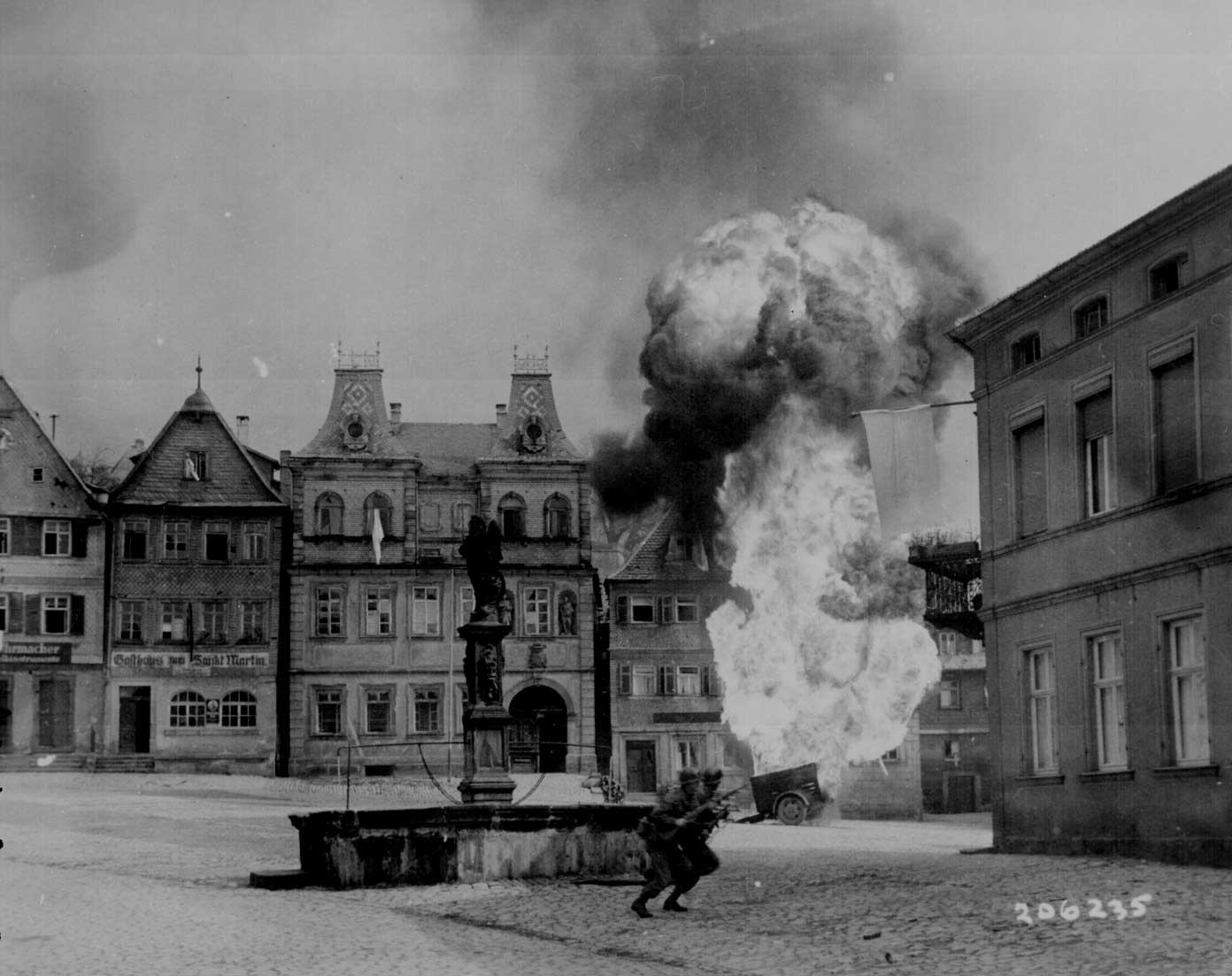 Men of US 101st Infantry Regiment running past a burning fuel trailer in square of Kronach, Bayreuth, Germany, 14 Apr 1945 (US National Archives: 111-SC-206235)