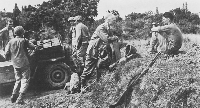 Ernie Pyle (center) talking to a Marine on Okinawa a few hours after its invasion, April 1945 (US Army Center of Military History)