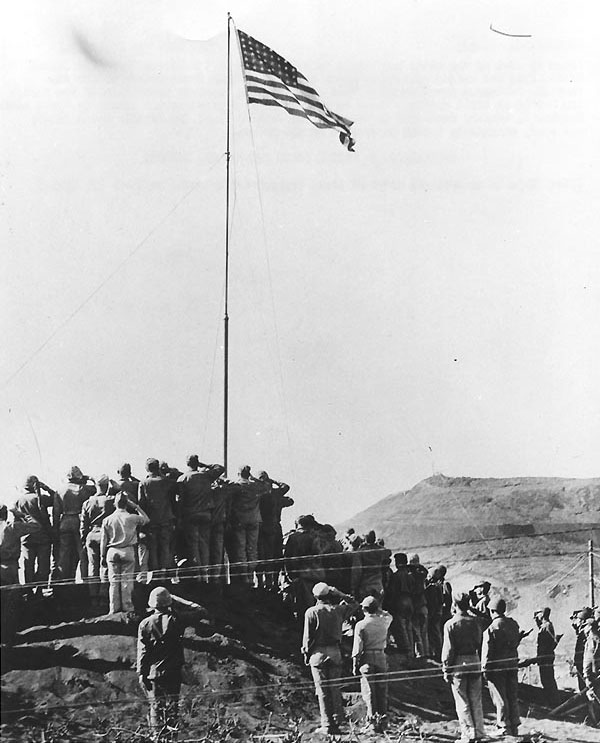 Flag raising at US Headquarters on Iwo Jima after US Navy military government is established, 14 Mar 1945. (US Naval History and Heritage Command: NH 104584)
