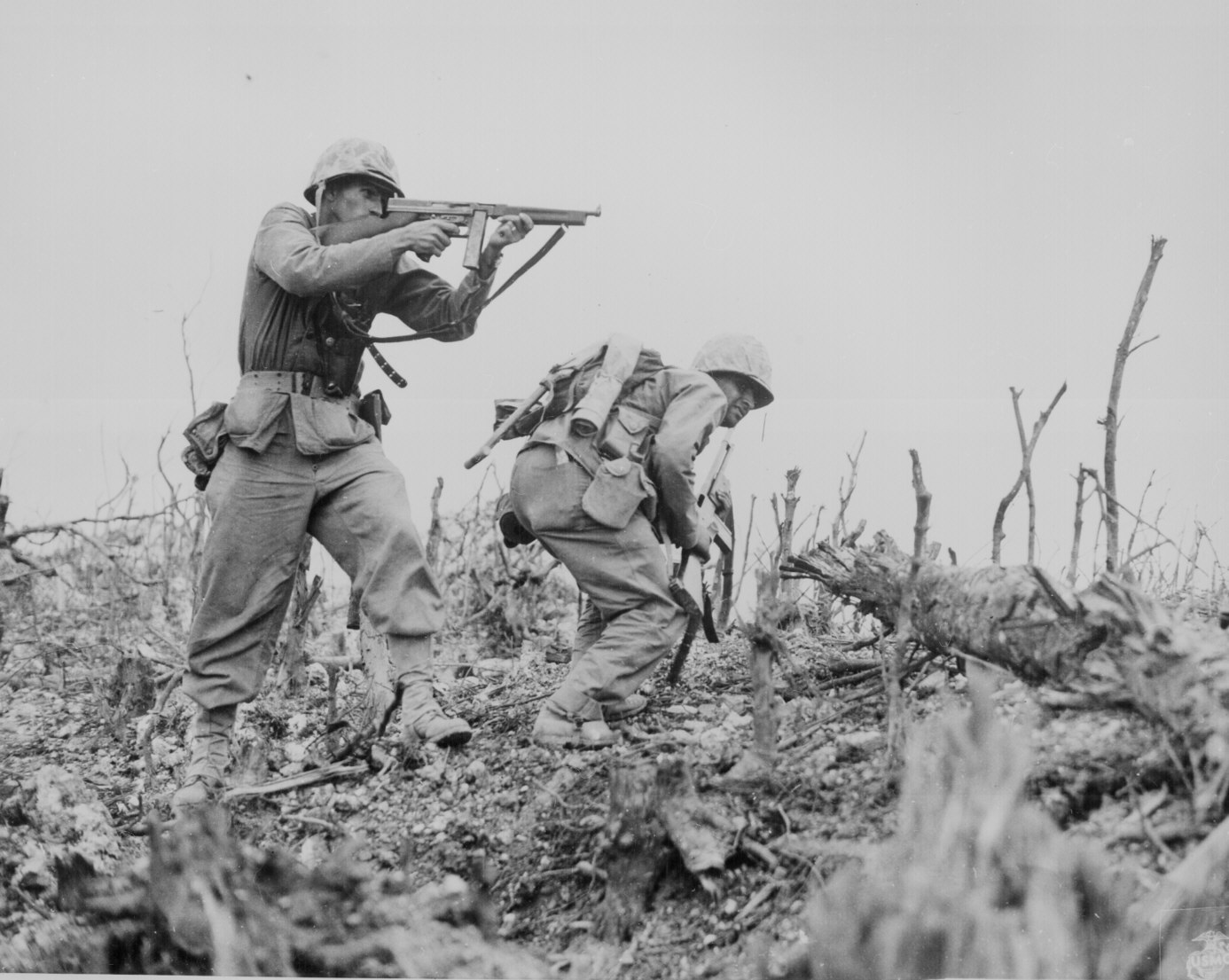 A Marine of the US 1st Marine Division pointed his Thompson submachine gun at a Japanese sniper, Okinawa, Apr-Jun 1945 (US National Archives: 127-N-123170)