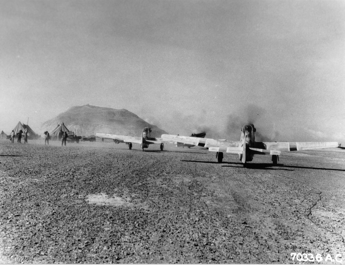 P-51D Mustangs of the US 47th Fighter Squadron on Iwo Jima prepare for raid on Chichi Jima, Mar 15, 1945; Mt. Suribachi in background (US Army Air Force photo)