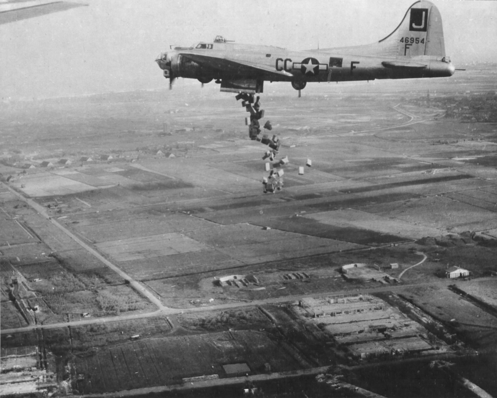 "B-17G Fortress ""Liquid-8-Or"" of 569th Bomb Squadron dropping cases of ""10 in 1"" rations into Holland during Operation Chowhound aimed at breaking the famine in western Holland, May 1 or 3 1945 (public domain via WW2 Database)"
