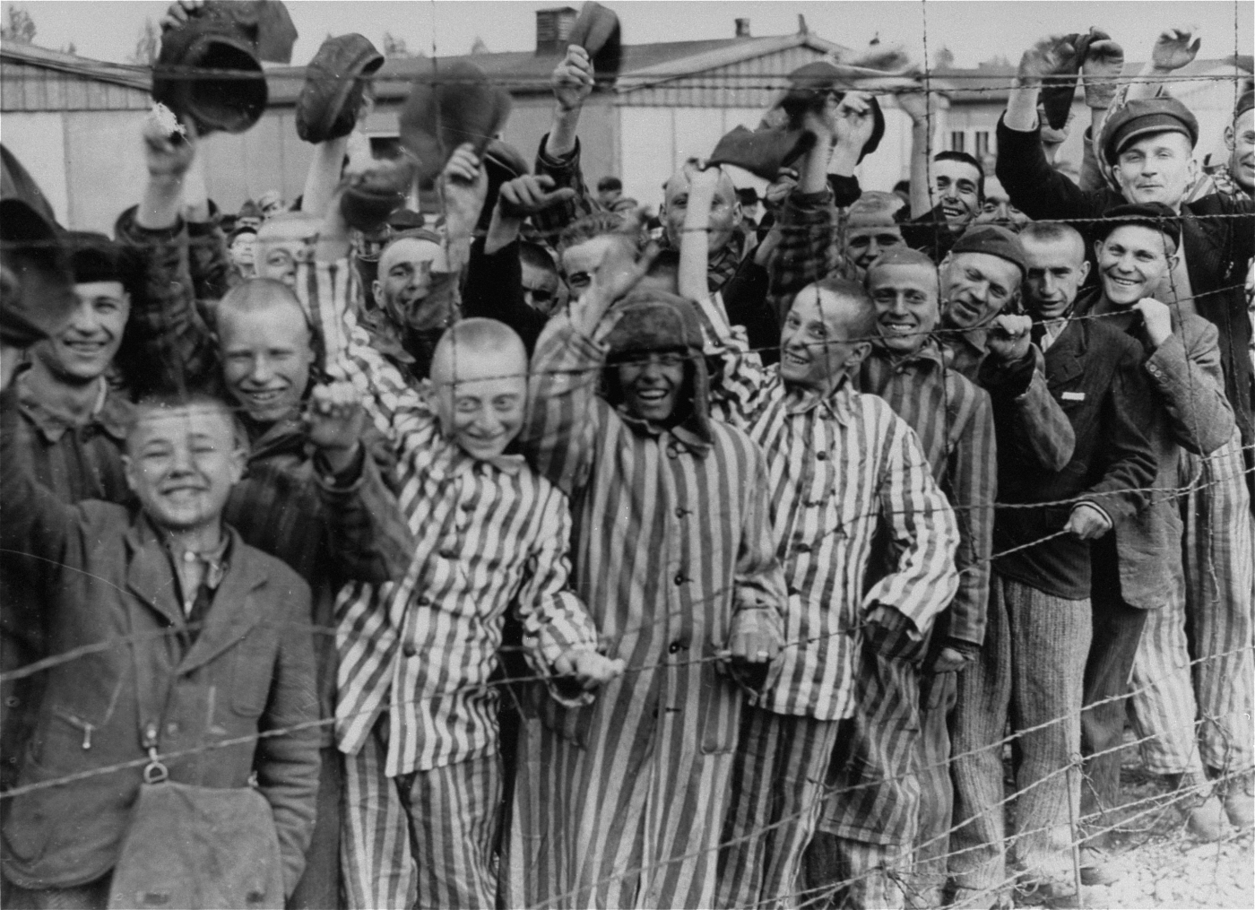 Prisoners celebrating the arrival of United States Army troops, Dachau Concentration Camp, Germany, 29 Apr 1945 (US Holocaust Memorial Museum: 45075)