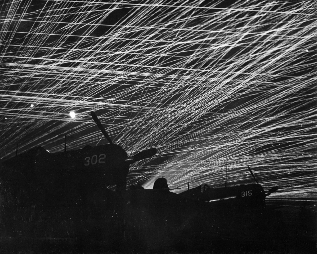 Anti-aircraft tracers in the night sky above Yontan Airfield, Okinawa, 28 Apr 1945; US Marine Corps F4U Corsair fighters in foreground (US National Archives: 127-G-118775)