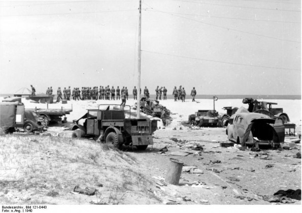 German troops look out over the English Channel with the wreckage of British equipment behind them (German Federal Archive: Bild 121-0443)