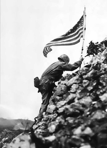 US Marine Lt. Col. R. P. Ross Jr. raising the US flag over Shuri castle on Okinawa, 29 May 1945 (US National Archives: FMC 42043)