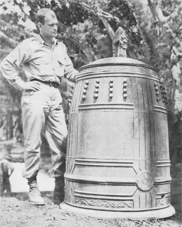 American officer standing by the bell from Shuri Castle on Okinawa, 1945 (US Army Center of Military History)