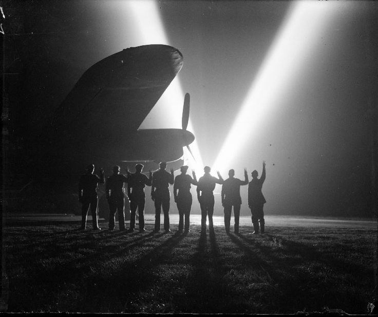Ground crew on a RAF Bomber Command station in Britain return the 'V for Victory' sign to a neighboring searchlight crew. Silhouetted is the nose of a Lancaster bomber. (Imperial War Museum)