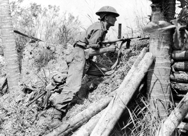 Soldier of the Australian 2/43rd Battalion armed with an Owen Gun in a bomber dispersal bay at Labuan airstrip, Brunei, Borneo, 10 June 1945. (Australian War Memorial: 018637)