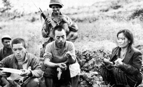 Japanese resistance fighters captured, Okinawa, Japan, Jun 1945; prisoner to the far left is reading American propaganda literature (US Army photo)