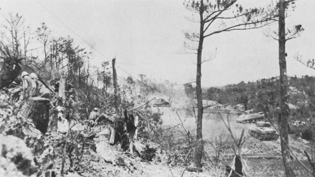 Yuza-Dake Hill, under attack by US 382nd Infantry, 96th Division. Tanks are working on the caves and tunnel system at base of ridge, June 1945 (US Army Center of Military History)