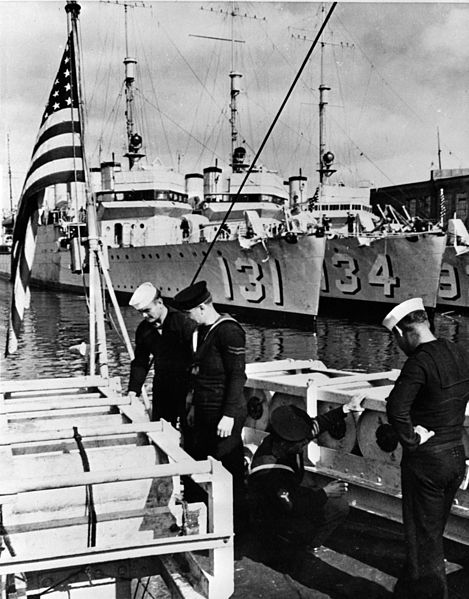 Royal Navy and US Navy sailors inspect depth charges aboard Wickes-class destroyers in 1940. In the background are USS Buchanan (DD-131), and USS Crowninshield (DD-134). On 9 September 1940 both were transferred to the Royal Navy. (Library of Congress)