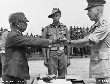 Lt. Gen. Hatazo Adachi symbolically surrenders his sword to Australian Maj. Gen. H.C.H. Robertson at Wom Airstrip, New Guinea, 13 September 1945 (Australian War Memorial: 019296)