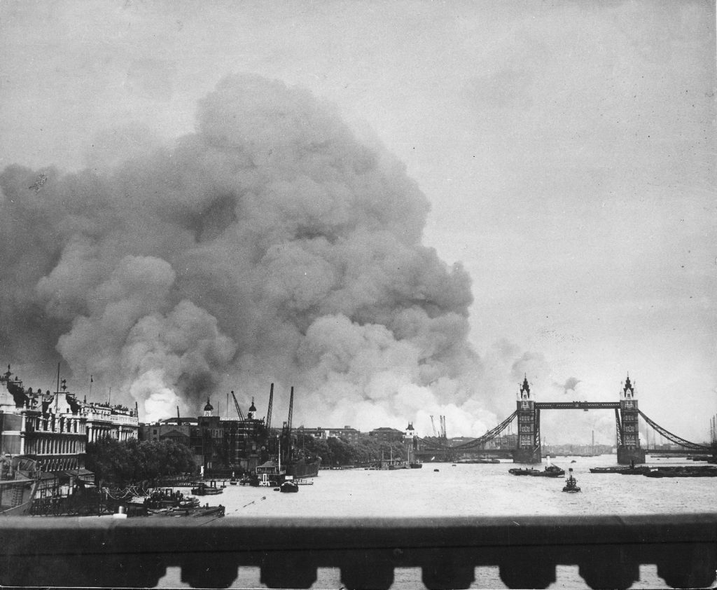 "Smoke rising from the Surrey Docks, London, England, 8 Sep 1940, the morning after the opening night of ""The Blitz,"" with the Tower Bridge silhouetted against the smoke (US National Archives: 541917)"