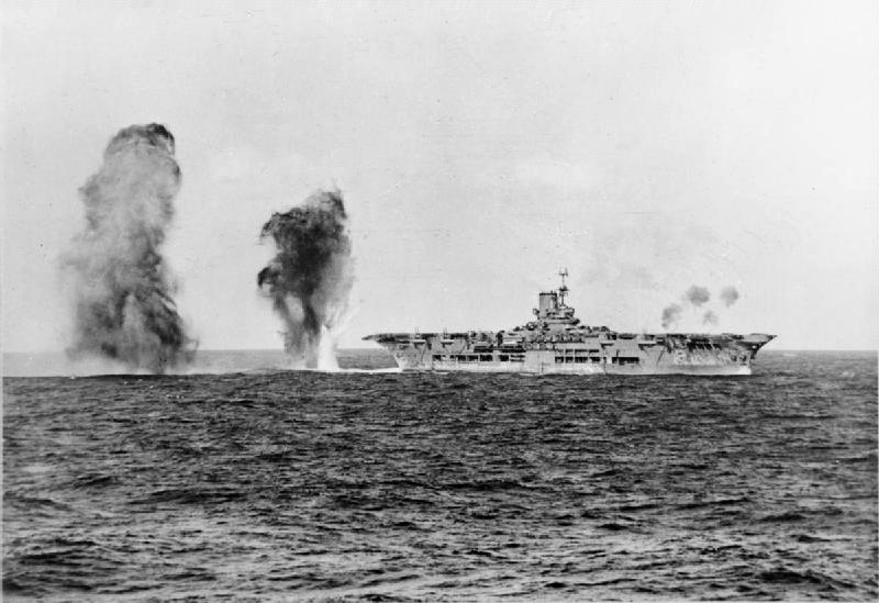 Bombs falling astern of HMS Ark Royal during attack by Italian aircraft during the Battle of Cape Spartivento, 27 Nov 1940; photograph taken from cruiser HMS Sheffield (Imperial War Museum: 4700-01 A 2298)