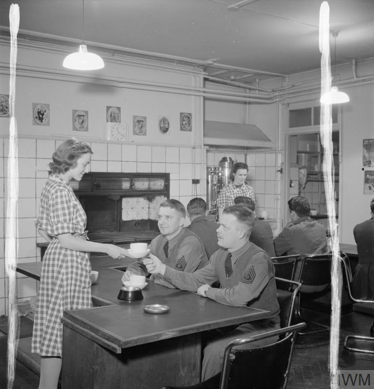 A female volunteer at the American Red Cross Eagle Club gives a cup of tea to one of several American soldiers making use of the canteen facilities at the club, WWII (Imperial War Museum: D 8333)