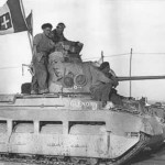 Matilda tank en route into Tobruk, Libya, 24 Jan 1941; note British soldiers displaying a captured Italian flag (Imperial War Museum: 4700-32 E 1772)