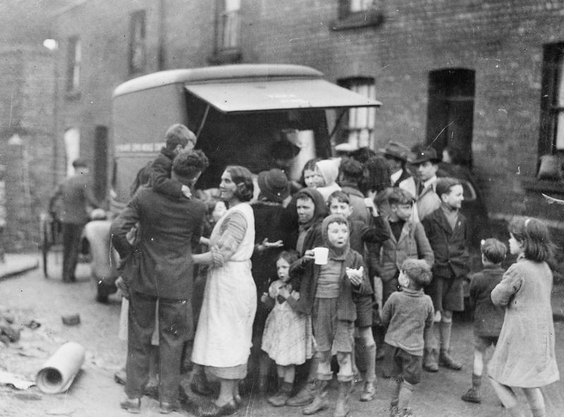 Mothers and children in a working class area of Swansea have tea and sandwiches from a mobile canteen after a night's bombing, WWII (Imperial War Museum: HU 36143)