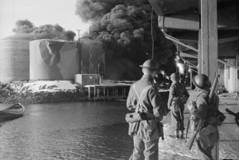 Raid on the Lofoten Islands: British Commandos watching fish oil tanks burning, 4 March 1941 (Imperial War Museum: N 396)