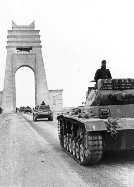 Panzer Mk IIIs and Mk IIs cross under the Marble Arch at Sirte, Libya, 21 March 1941 (German Federal Archive: Bild 101I-782-0009-01A)