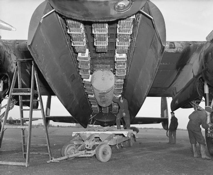 Bomb bay of an Avro Lancaster of No.57 Squadron RAF at Scampton, Lincolnshire, loaded with a 4000-lb impact-fused HC bomb ('cookie') and 12 Small Bomb Containers (SBCs) loaded with incendiaries, WWII (Imperial War Museum: CH 18371)
